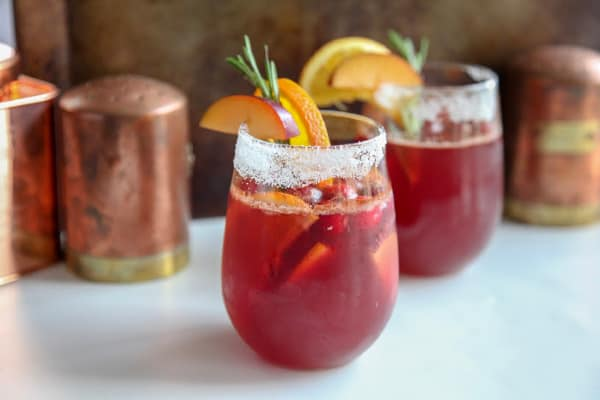 This easy Christmas punch is made with fresh ingredients like ginger ale, cranberry juice, plums and orange with a touch of cinnamon. Makes a great cocktail or mocktail for december holiday parties.