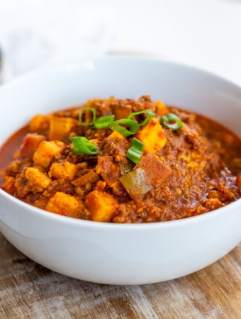 Chili in a bowl next to a spoon