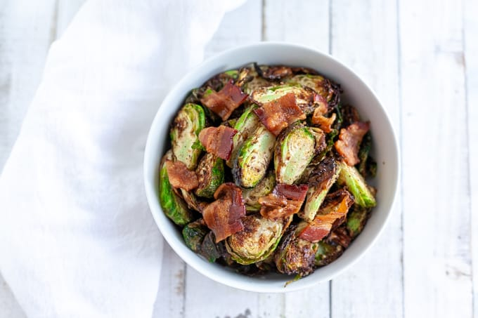 air fryer brussels sprouts and bacon in a white bowl