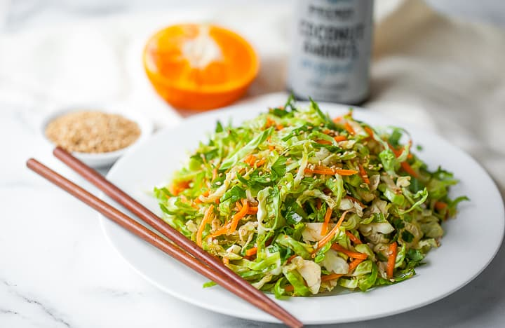shaved brussels sprouts on a white plate with chopsticks